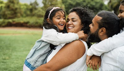 Happy indian family having fun outdoor - Hindu parents laughing with their children at city park