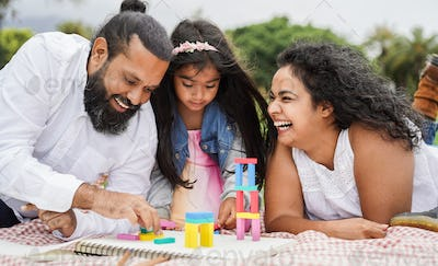 Indian parents having fun at city park playing with wood toys with their daughter