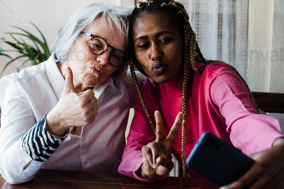 Multiracial young and senior people taking a selfie with mobile phone - Focus on faces