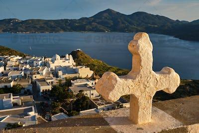 Christian cross and Plaka village on Milos island over red geranium flowers on sunset in Greece