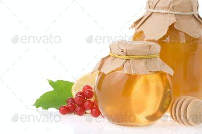 glass jar full of honey on white