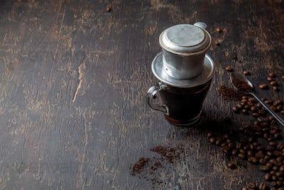 Preparation of Vietnamese coffe with vietnamese coffe filer on dark background