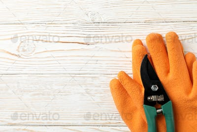 Gloves and pruning shears on wooden background, space for text