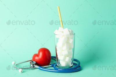 Glass with sugar cubes, heart and stethoscope on mint background