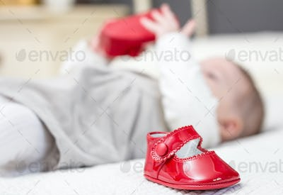 Baby red shoes and babe playing on the background