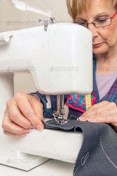 Senior seamstress woman working on sewing machine