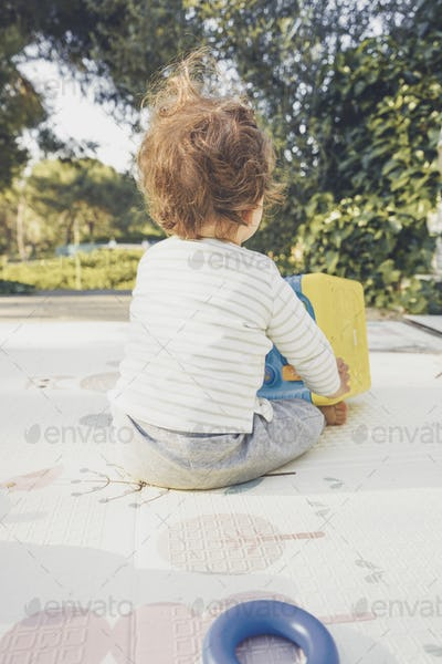 Backview of a baby playing in nature