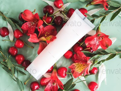Skin care flat lay with cream tube with cherries and flowers in water on natural green background