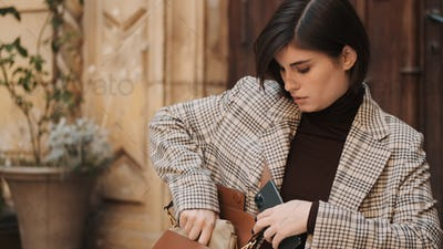 Beautiful stylish businesswoman dressed in plaid blazer hiding s