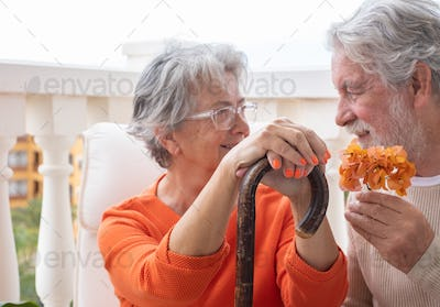 Senior woman suffering from back pain sits with hands resting on the cane looking at her husband