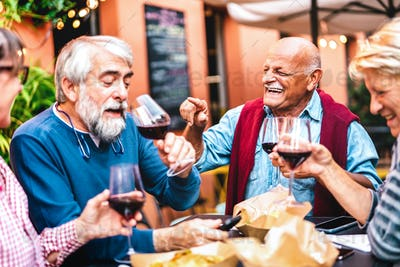 Happy retired friends having fun drinking red wine at pre dinner party