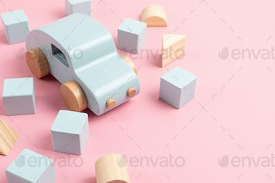 Eco friendly child wooden toys, blue car and construction bricks over pink background