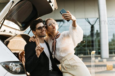 Charming blonde woman blows kiss, hugs boyfriend and takes selfie with him. Handsome man in eyeglas