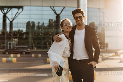Brunette happy man in white shirt and black suit hugs attractive girlfriend near airport. Charming