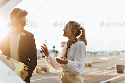 Happy blonde woman in white blouse talks with boyfriend outside. Charming man in black jacket and s