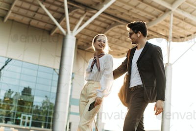 Cheerful man in black suit, sunglasses hugs girlfriend in white blouse and beige pants. Attractive