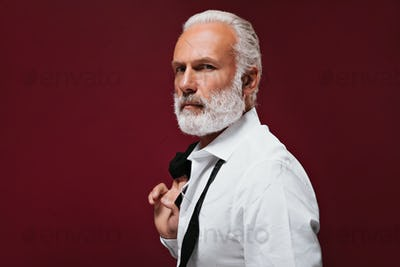 Adult man in white shirt looks into camera. Charming guy with grey hair in modern black suit posing