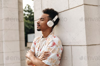 Portrait of bearded dark-skinned curly man in floral shirt and white headphones leans on wall and p