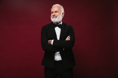 Man in black classic style outfit smiling on burgundy background. fashionable guy with grey hair in