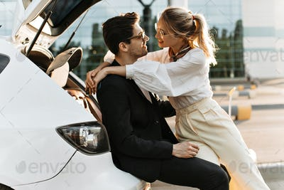 Happy woman in white blouse, beige pants and eyeglasses smiles and looks at boyfriend. Man in black