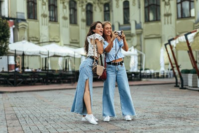 Surprised brunette woman in stylish denim pants and white floral blouse poses with her friend outsi