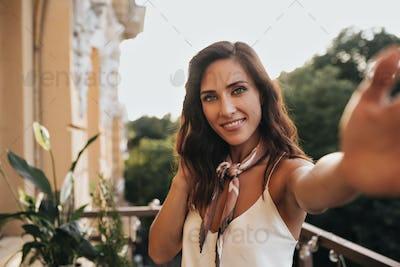 Attractive lady in silk white top takes selfie on balcony. Pretty brunette woman in beige shawl mak