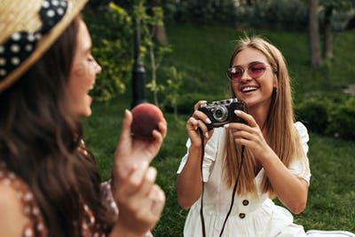 Cheerful girlfriends in stylish summer dresses smile and have picnic outside. Cool blonde lady in r