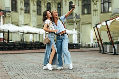 Brunette and blonde women in jeans and floral blouses take selfie outside. Happy young lady in deni