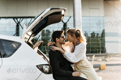 Handsome man in black jacket smiles, looks at girlfriend with love and sits in car. Blonde woman in