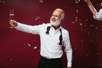 Happy man in white shirt holds champagne glass on confetti background. Joyful grey haired guy in st