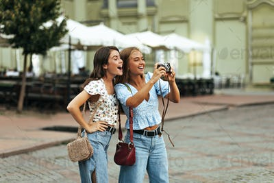Cheerful excited tanned girls in stylish floral blouses and denim pants smile sincerely outside. Bl