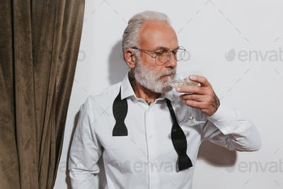 Stylish man in eyeglasses drinking champagne. Bearded adult in fashionable clothes and glasses posi