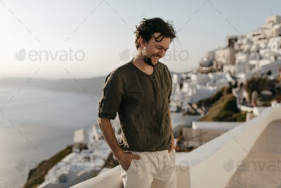 Cheerful happy brunette man in dark-green t-shirt and white shorts smiles sincerely outside. Young