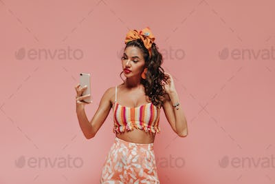 Bright tanned woman with orange bandana and stylish earrings in striped top and printed pink pants