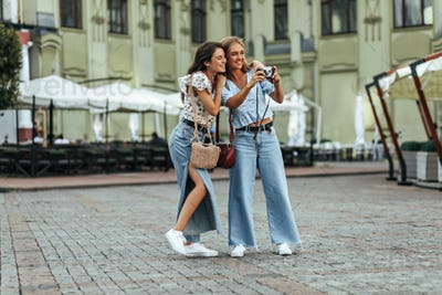 Happy joyful brunette and blonde women in jeans and floral blouses hug and laugh outside. Charming