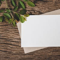 A blank card is placed on envelope and leaf with wood background