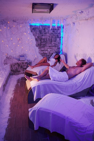 Two people in white towels lying down on beds indoor in room with violet decor
