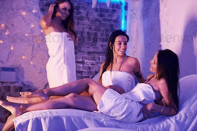 Young women in white towels lying down on beds indoor in room with violet decor
