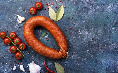 sausage circle on blue kitchen table with spices, tomatoes and garlic, natural organic meat product