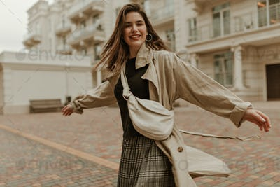 Good humored young woman in stylish trench coat and grey checkered skirt moves outside and smiles.