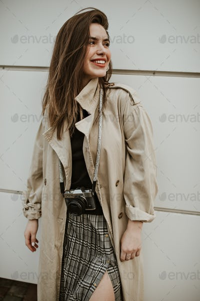 Cheerful attractive woman in checkered skirt and stylish midi beige trench coat smiles, looks away