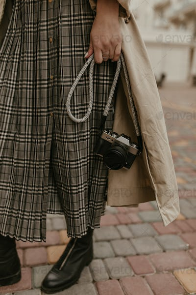 Woman in grey checkered skirt, black boots and beige midi trench coat holds retro camera and poses
