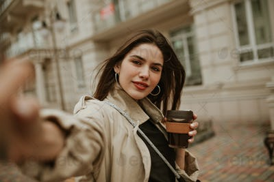 Brown-eyed brunette charming woman in beige trench coat takes selfie, smiles and holds coffee cup o