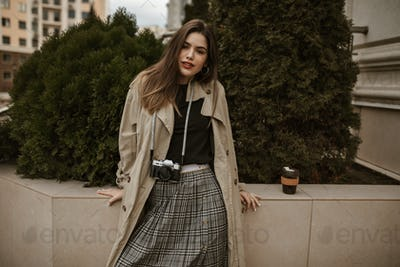 Brown-eyed attractive woman in beige trench coat and checkered dark skirt leans on fence and poses