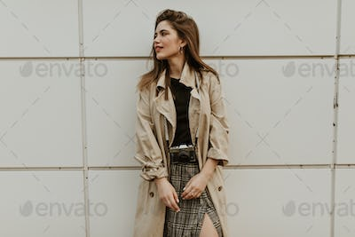 Portrait of attractive lady in checkered midi skirt and beige trench coat looks away and poses with