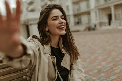 Brunette charming woman in beige trench coat and black t-shirt smiles sincerely, sits on wooden ben