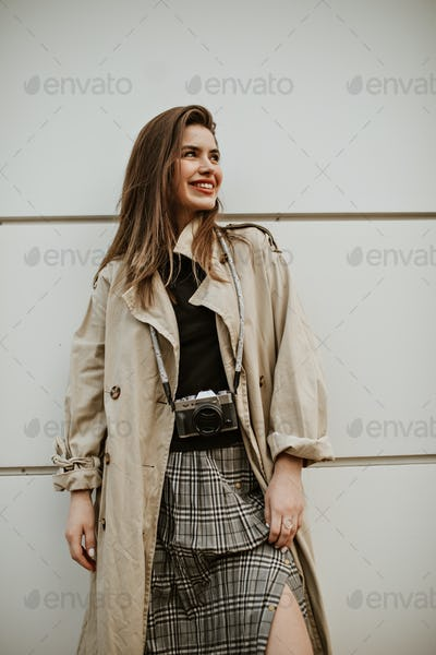 Happy young lady in stylish grey skirt, black top and beige trench coat smiles sincerely and poses
