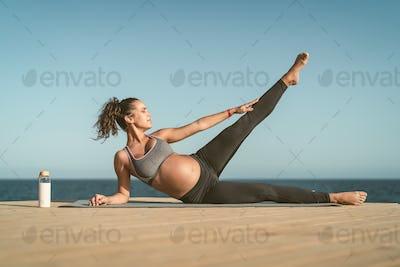 Young pregnant woman doing prenatal pilates exercises session next the sea