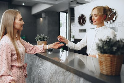 Young woman hotel guest receiving key card from receptionist