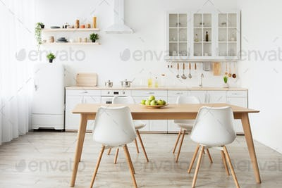 Dining room and stylish design. Wooden table and white chairs, kitchen utensils on furniture and